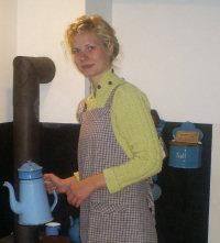 Edith er ved at lave kaffe til turen. Hun pakker kaffekanden ind i aviser og et viskestykke, så kanden holder på varmen nede i kurven.
