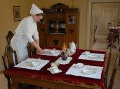 Kokkepigen dækker et smukt Kaffebord til dagens Gæster