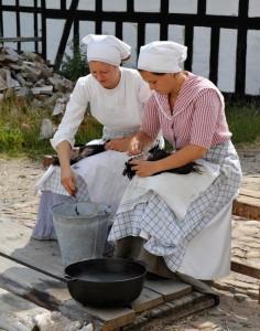 Pigerne i gang med at plukke hanekyllinger til pinsefrokosten.